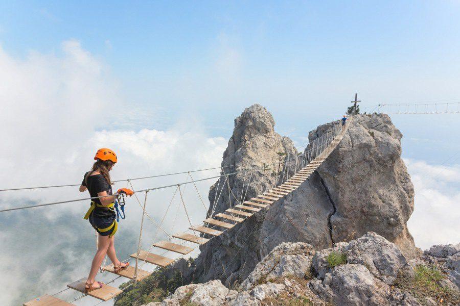 Gephyrophobia Fear of Bridges - woman on a mountain rope bridge
