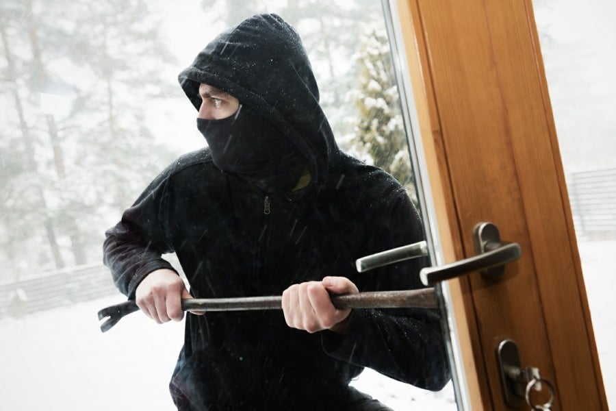 fear of being robbed harpaxophobia - burglar breaking into house with crowbar