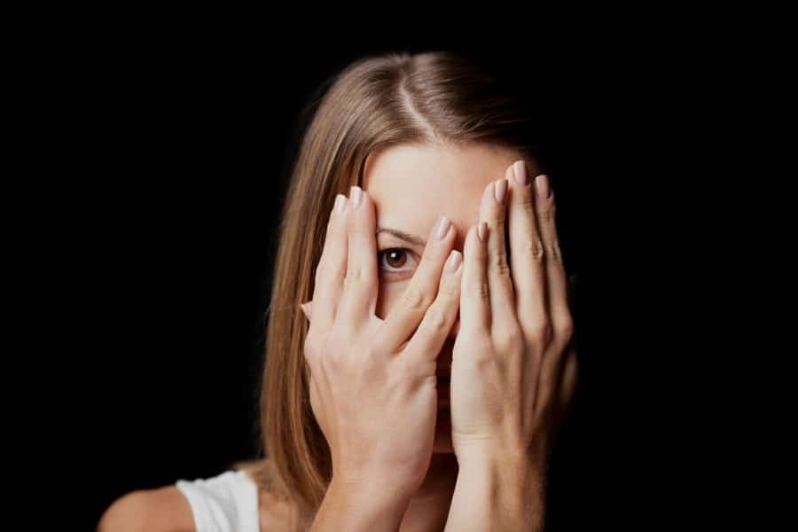 fear of being stared at scopophobia - girl hiding her face with her hands to avoid being stared at