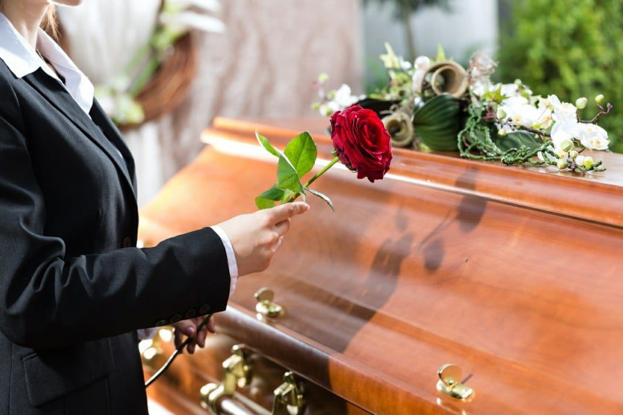 thanatophobia is the fear of death or dying - woman standing next to coffin with red rose