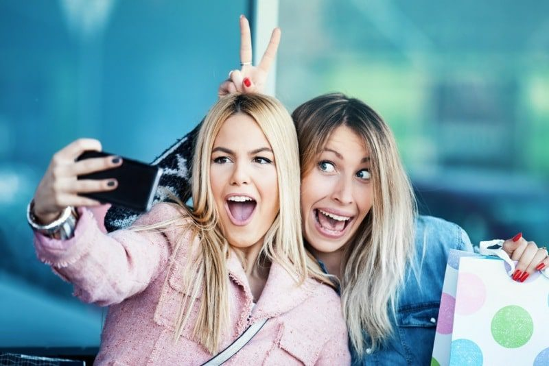 cherophobia is the fear of being happy or having fun - two girls taking selfies