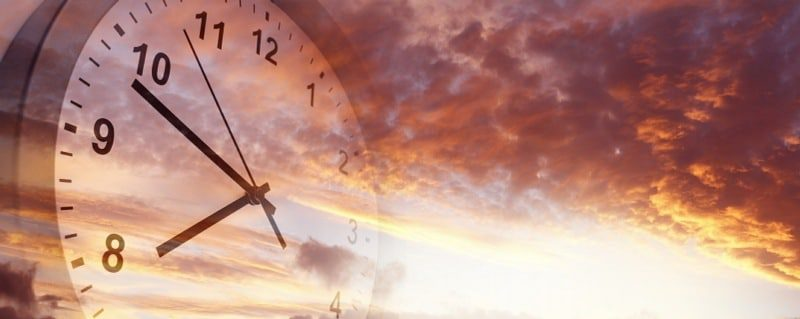 fear of passing time chronophobia - clock superimposed over sunset sky