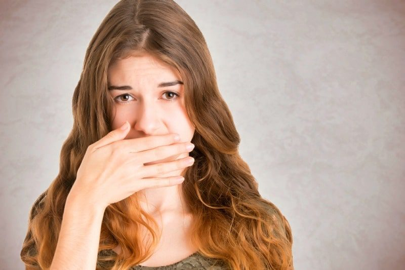 blushing problems, also know as erythrophobia - woman blushing and covering mouth