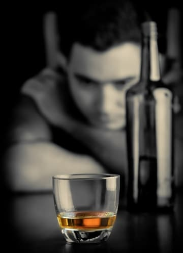 alcohol addiction? Man looking at drink of scotch